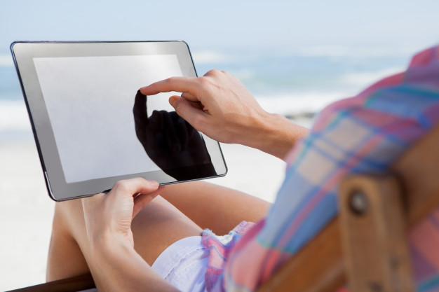 woman-sitting-on-beach-in-deck-chair-using-tablet-pc_13339-564171jpg